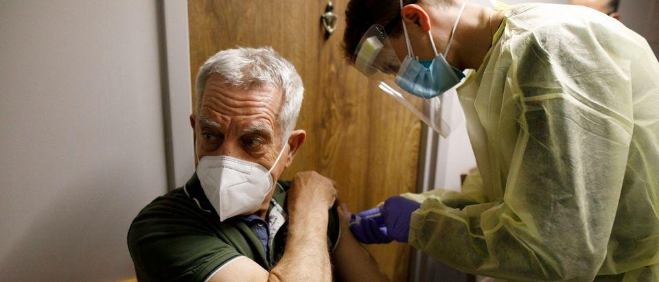 A senior citizen receives his second dose of teh Pfizer COVID-19 vaccine in Toronto. Photo by Cole Burston. Getty.