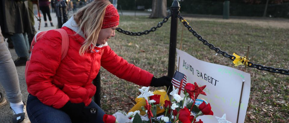 Melody Black, from Minnesota, becomes emotional as she visits a memorial near the U.S. Capitol Building for Ashli Babbitt who was killed in the building on January 06, 2021 in Washington, DC. (Photo by Joe Raedle/Getty Images)