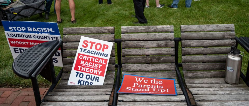 """Signs are seen on a bench during a rally against """"critical race theory"""" (CRT) being taught in schools at the Loudoun County Government center in Leesburg, Virginia on June 12, 2021. - """"Are you ready to take back our schools?"""" Republican activist Patti Menders shouted at a rally opposing anti-racism teaching that critics like her say trains white children to see themselves as """"oppressors."""" """"Yes!"""", answered in unison the hundreds of demonstrators gathered this weekend near Washington to fight against """"critical race theory,"""" the latest battleground of America's ongoing culture wars. The term """"critical race theory"""" defines a strand of thought that appeared in American law schools in the late 1970s and which looks at racism as a system, enabled by laws and institutions, rather than at the level of individual prejudices. But critics use it as a catch-all phrase that attacks teachers' efforts to confront dark episodes in American history, including slavery and segregation, as well as to tackle racist stereotypes. (Photo by Andrew Caballero-Reynolds/AFP via Getty Images)"""