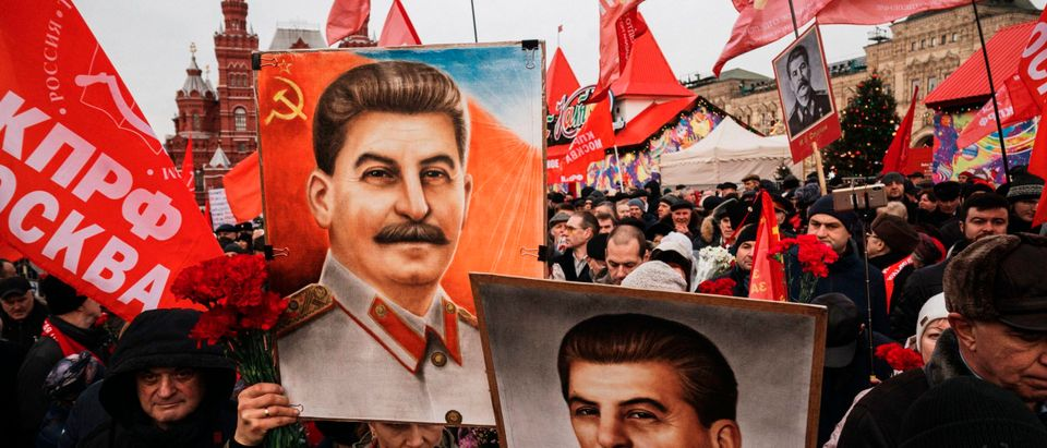 People hold portraits of Soviet leader Joseph Stalin and wait to lay flowers at his grave outside the Kremlin on the Red Square in Moscow on December 21, 2019.(Photo by DIMITAR DILKOFF/AFP via Getty Images)
