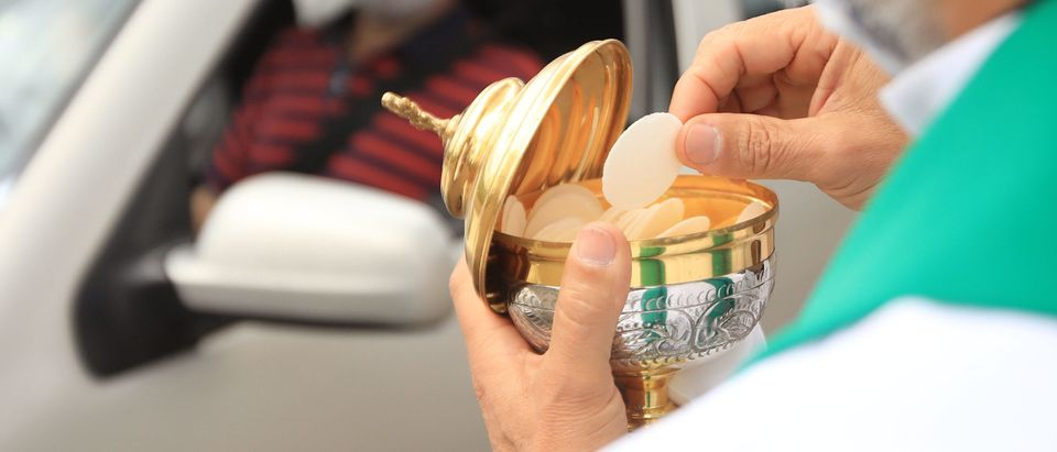 A priest offers communion to a Catholic during a drive-in mass celebrated in a parking lot due to the COVID-19 on August 23, 2020 (Photo by DANIEL MUNOZ/AFP via Getty Images)
