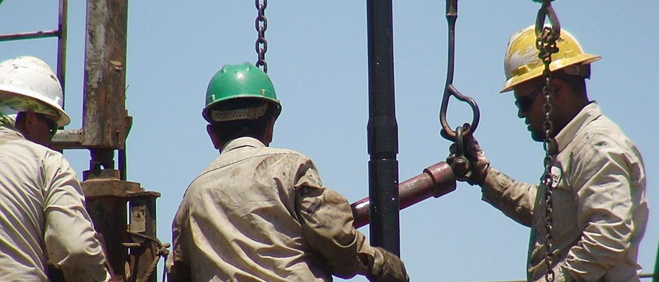 Oil workers on a rig in Midland County, Texas. (Photo by MIRA OBERMAN/AFP via Getty Images)