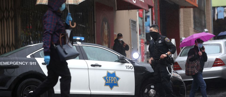 San Francisco police officer William Ma stands guard on a street corner in Chinatown on March 18, 2021 in San Francisco, California. (Photo by Justin Sullivan/Getty Images)