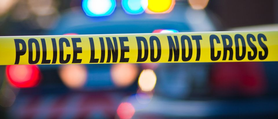 Police tape with flashing lights [Shutterstock]