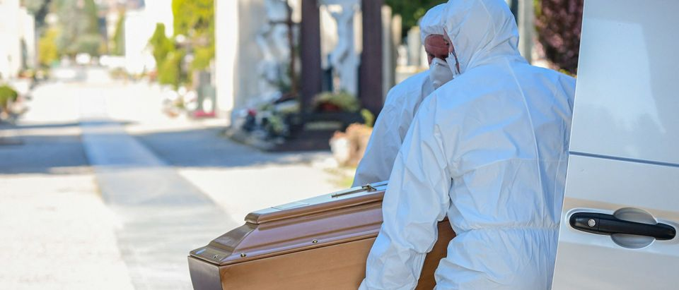 Undertakers wearing a face mask and overalls unload a coffin out of a hearse on March 16, 2020 at the Monumental cemetery of Bergamo, Lombardy, as burials of people who died of the new coronavirus are being conducted at the rythm of one every half hour. (Photo by Piero Cruciatti/AFP via Getty Images)