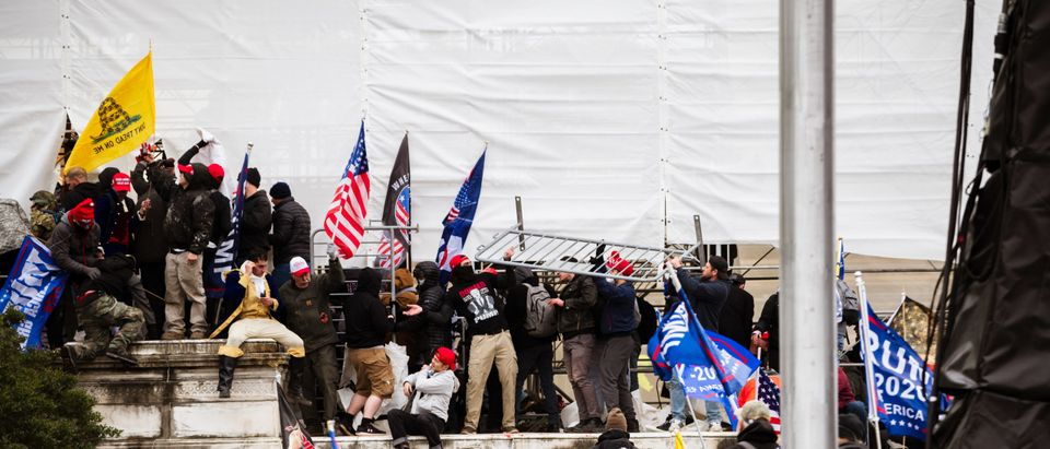 A group of pro-Trump protesters climb the walls of the Capitol Building after storming the West lawn on January 6, 2021 in Washington, DC. (Photo by Jon Cherry/Getty Images)