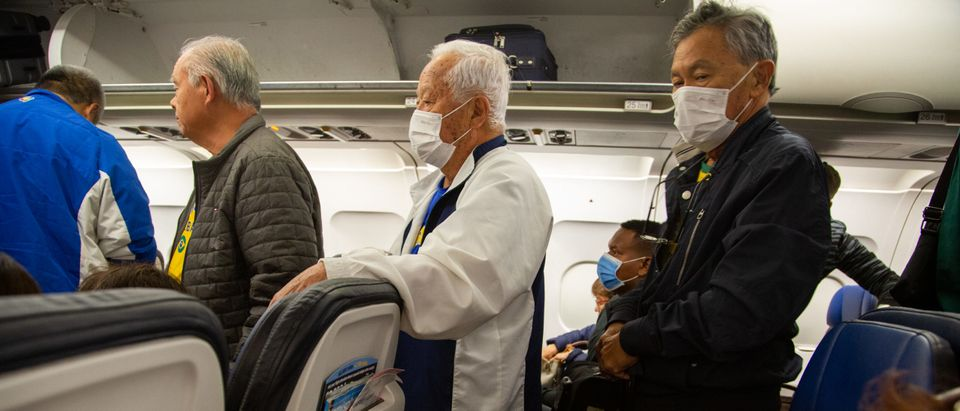 Passengers wear protective face masks in an airplane after arrival in Houston International Airport on March 14, 2020 in Houston, Texas. (Photo by Carol Coelho/Getty Images)
