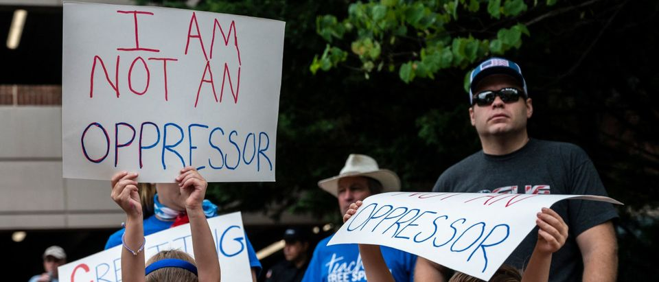 """People hold up signs during a rally against """"critical race theory"""" beign taught in schools at teh Loudoun County Government center in Leesburg, Virginia on June 12, 2021. Photo by Andrew Caballero-Reynolds. Getty."""