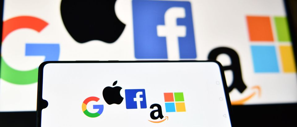 An illustration picture taken in London on December 18, 2020 shows the logos of Google, Apple, Facebook, Amazon and Microsoft displayed on a mobile phone and a laptop screen. (Photo by JUSTIN TALLIS/AFP via Getty Images)