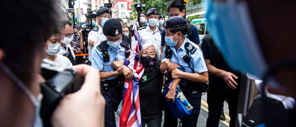 Activist Alexandra Wong is taken away by police while protesting on the 24th anniversary of Hong Kong's handover from Britain. (Photo by ISAAC LAWRENCE/AFP via Getty Images)