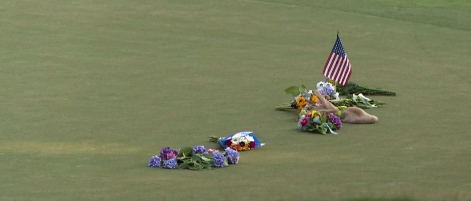 Flags and flowers form a memorial for Gene Siller at the tenth hole of Pinetree Country Club. (YouTube/Screenshot/Associated Press)