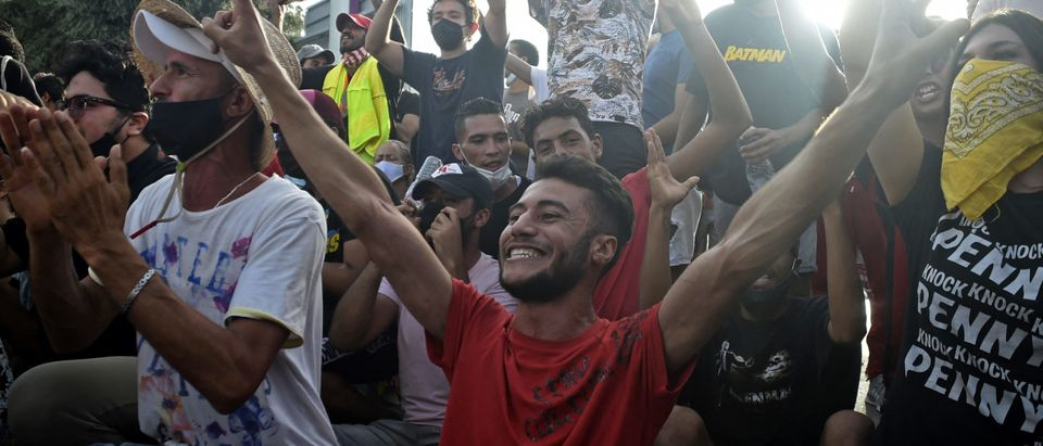 Supporters cheer outside the army-barricaded parliament building in the capital Tunis on July 26, 2021. (Photo by YASSINE MAHJOUB/AFP via Getty Images)