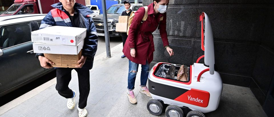 A woman taking a food bag out of a Yandex.Rover, an autonomous delivery robot. (Photo by YURI KADOBNOV/AFP via Getty Images)