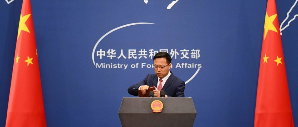 Chinese Foreign Ministry spokesman Zhao Lijian packs up his notes after speaking at the daily media briefing in Beijing on April 8, 2020. (Photo by GREG BAKER/AFP via Getty Images)