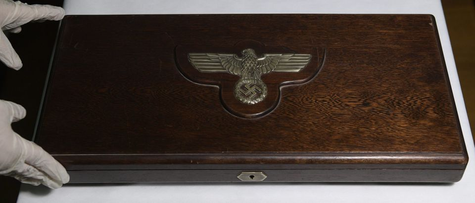 A member of the Department of Protection of the Cultural Heritage of the Federal Police holds wooden box with the Nazi eagle containing four magnifiers, on display with the rest of the 75 pieces of Nazi art seized during an operation carried out on June 9, on the outskirts of Buenos Aires at the Interpol headquarters in Buenos Aires, on June 22, 2017. (JUAN MABROMATA/AFP via Getty Images)