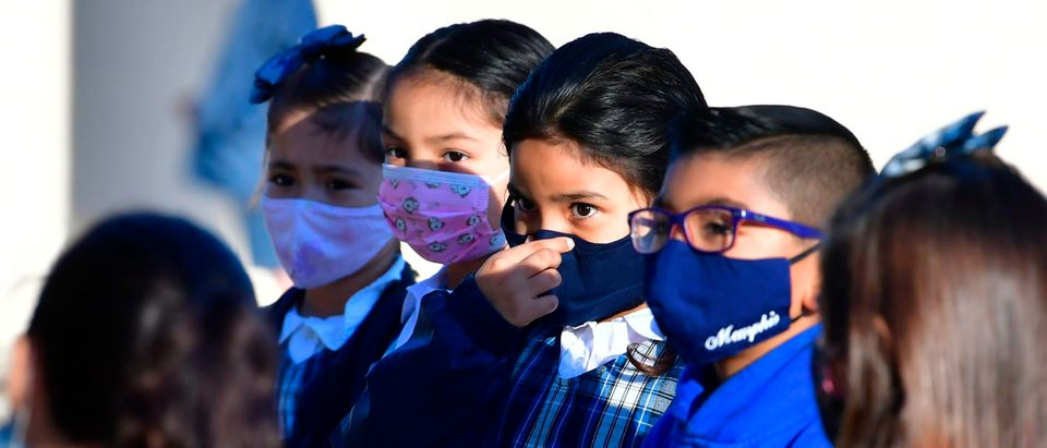 A students adjusts her facemask at St. Joseph Catholic School in La Puente, California on November 16, 2020, where pre-kindergarten to Second Grade students in need of special services returned to the classroom today for in-person instruction. - The campus is the second Catholic school in Los Angeles County to receive a waiver approval to reopen as the coronavirus pandemic rages on. The US surpassed 11 million coronavirus cases Sunday, adding one million new cases in less than a week, according to a tally by Johns Hopkins University. (Photo by Frederic J. BROWN / AFP) (Photo by FREDERIC J. BROWN/AFP via Getty Images)