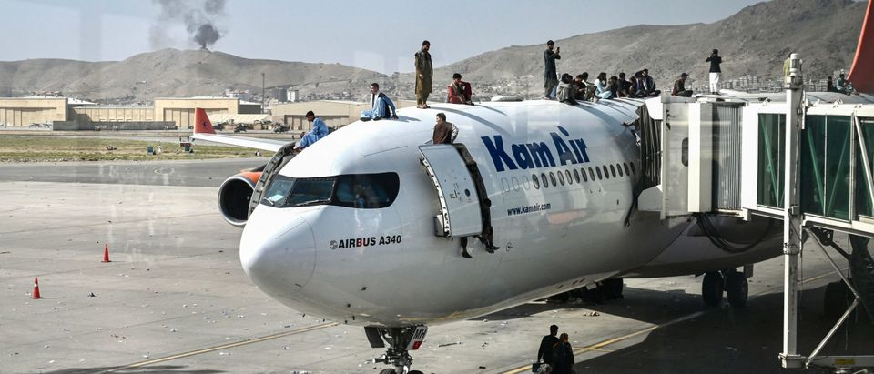 Afghan people climb atop a plane as they wait at the Kabul airport in Kabul on August 16, 2021, after a stunningly swift end to Afghanistan's 20-year war, as thousands of people mobbed the city's airport trying to flee the group's feared hardline brand of Islamist rule. (Photo by Wakil Kohsar / AFP) (Photo by WAKIL KOHSAR/AFP via Getty Images)