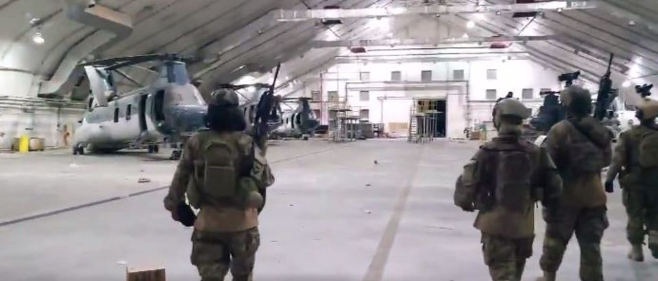 Taliban fighters enter a hangar at the Kabul airport wearing U.S. military gear. (Screenshot/Twitter/Nahib Bulos and the Los Angeles Times)