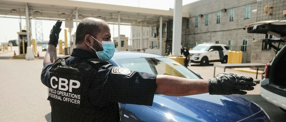 U.S. Customs and Border Protection agents direct vehicles re-entering the U.S. from Canada, which has opened its borders to U.S. citizens who can provide proof of vaccination and a negative Covid-19 test. (Photo by Matthew Hatcher/Getty Images)