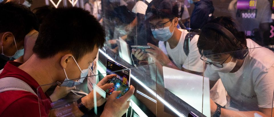 Visitors play video games at the annual Animation-Comic-Game in Hong Kong on July 24, 2021. (Photo by BERTHA WANG/AFP via Getty Images)