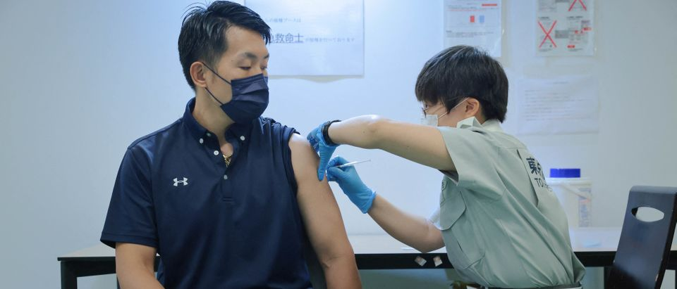 A Tokyo fire brigade staff member administers a dose of the Covid-19 coronavirus vaccine at Aoyama University in Tokyo on August 2, 2021. (Photo by STANISLAV KOGIKU/POOL/AFP via Getty Images)