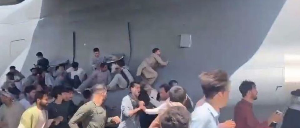 Afghans cling to a departing U.S. aircraft in a bid to escape Kabul. (Screenshot/Twitter/Mukhtar Wufayee)