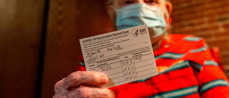 A man holds his CDC vaccine card after being inoculated with the Johnson & Johnson Covid-19 Vaccine. (Photo by JOSEPH PREZIOSO/AFP via Getty Images)