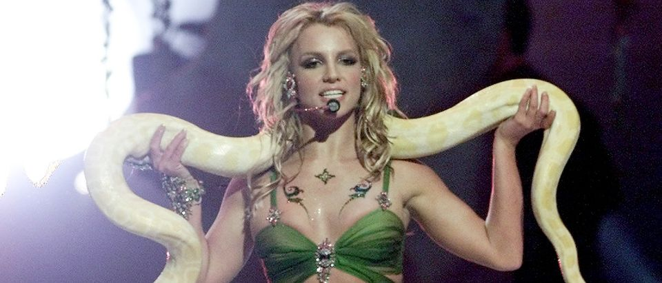 Singer Britney Spears performs with a snake draped