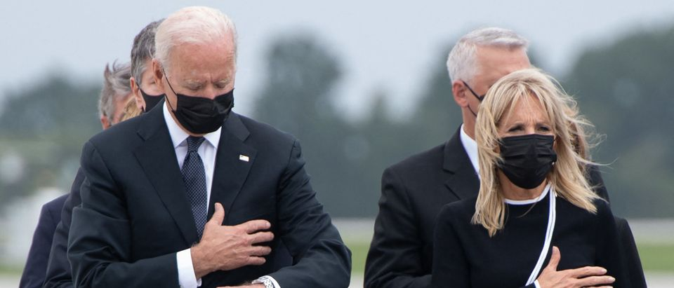 TOPSHOT - US President Joe Biden looks down alongside First Lady Jill Biden as they attend the dignified transfer of the remains of a fallen service member at Dover Air Force Base in Dover, Delaware, August, 29, 2021, one of the 13 members of the US military killed in Afghanistan last week. - President Joe Biden prepared Sunday at a US military base to receive the remains of the 13 American service members killed in an attack in Kabul, a solemn ritual that comes amid fierce criticism of his handling of the Afghanistan crisis. Biden and his wife, Jill, both wearing black and with black face masks, first met far from the cameras with relatives of the dead in a special family center at Dover Air Force Base in Delaware.The base, on the US East Coast about two hours from Washington, is synonymous with the painful return of service members who have fallen in combat. (Photo by SAUL LOEB / AFP) (Photo by SAUL LOEB/AFP via Getty Images)