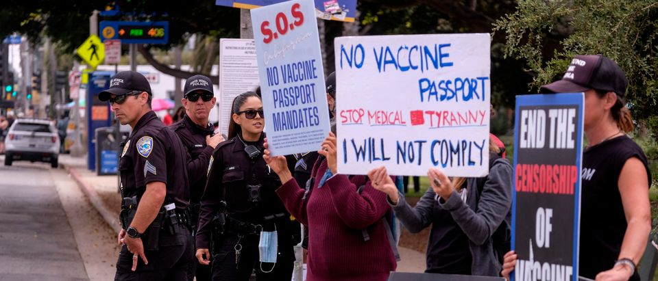 Santa Monica police officers watch as anti-vaccination protesters take part in a rally against Covid-19 vaccine mandates, in Santa Monica, California, on August 29, 2021. (Photo by Ringo Chiu/AFP via Getty Images)