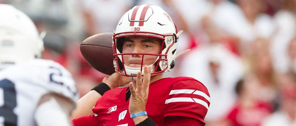 Sep 4, 2021; Madison, Wisconsin, USA; Wisconsin Badgers quarterback Graham Mertz (5) throws a pass under pressure from Penn State Nittany Lions linebacker Curtis Jacobs (23) during the second quarter at Camp Randall Stadium. Mandatory Credit: Jeff Hanisch-USA TODAY Sports via Reuters