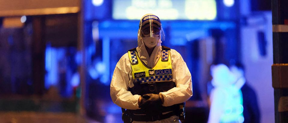A police officer wearing protective gear monitors the arrival of more than 90 Australian citizens. (Photo by TREVOR COLLENS/AFP via Getty Images)