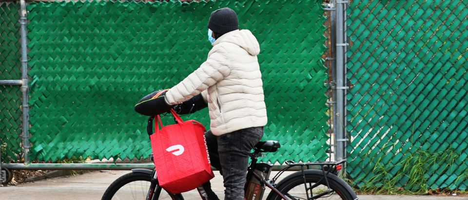 A Doordash delivery person rides their bike on Church Avenue in the Flatbush neighborhood of Brooklyn on December 04, 2020 in New York City. (Photo by Michael M. Santiago/Getty Images)