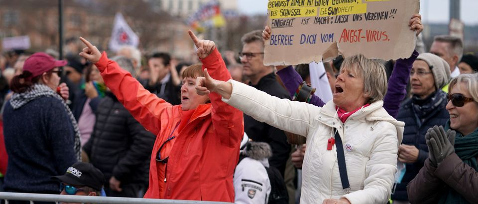 Supporters of the Querdenken movement cheer at a rally for what they claim are their basic rights during the third wave of the coronavirus pandemic on April 03, 2021 in Stuttgart, Germany. (Photo by Thomas Niedermueller/Getty Images)