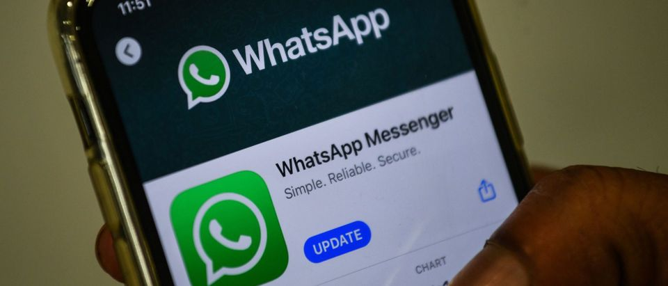 In this photo illustration taken on November 6, 2020, a user updates Facebook's WhatsApp application on his mobile phone. (Photo by INDRANIL MUKHERJEE/AFP via Getty Images)