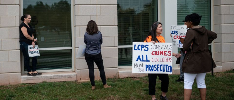 Protesters and activists hold signs as they stand outside a Loudoun County Public Schools (LCPS) board meeting in Ashburn, Virginia on October 12, 2021. (Photo by ANDREW CABALLERO-REYNOLDS/AFP via Getty Images)